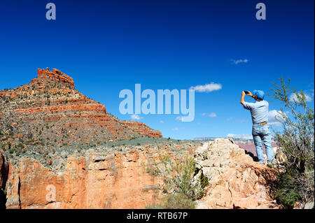 Hiker taking a picture  of a mesa from the Bright Angel Trail, Grand Canyon, Arizona, USA. - Stock Image