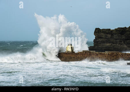 Storm Freya battering the Cornish coast with huge powerful waves breaking over the historic Monkey Hut on the pier at Portreath in Cornwall. - Stock Image