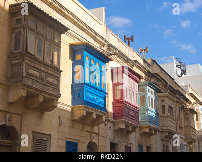Colorful wooden balconies hanging on the building facades are typical sights in and around Valetta in Malta - Stock Image
