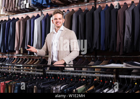 happy russian  male shopping assistant offering various suits in men's cloths store - Stock Image