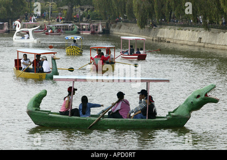 Visitors to Burnham Park in Baguio City, Philippines, enjoy paddling in colorful boats on the park's pond. - Stock Image