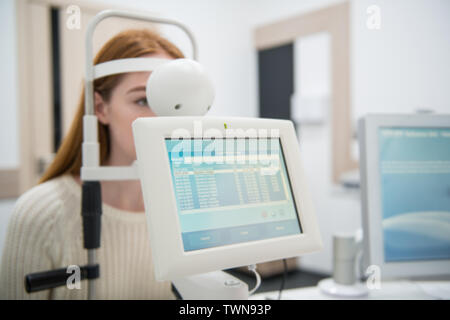 young girl patient on reception at doctor ophthalmologist. diagnostic ophthalmologic equipment. medicine concept - Stock Image
