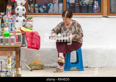 Woman sifting sunflower seeds Prenjass village market Albania - Stock Image