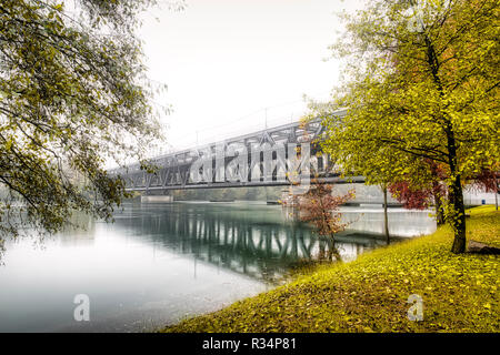 iron bridge on Ticino river in flood during the rainy season with milky sky in background - Stock Image