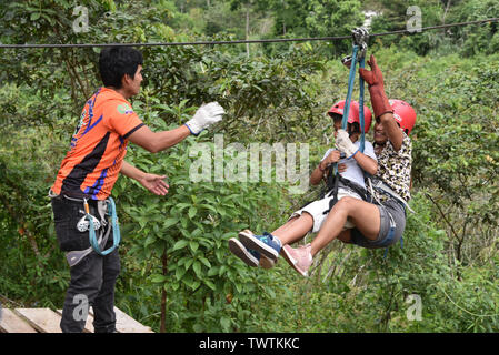 Junin, Peru - Dec 31, 2018: Adventurous tourists ziplining over a river in the Chanchamayo region - Stock Image