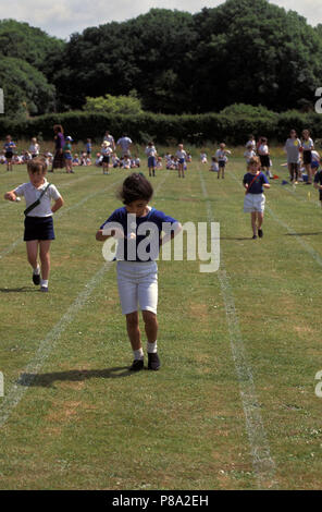children participating in egg and spoon race at primary school sports day - Stock Image