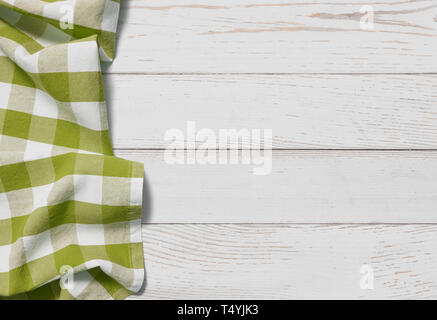 green folded tablecloth with white wooden table - Stock Image
