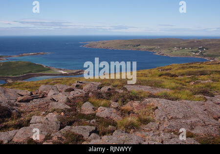 A view out to Isle Ristol, Reiff and Altandhu from Meail Dearg, Scotland with deep blue sea with rocks and heather in the foreground - Stock Image