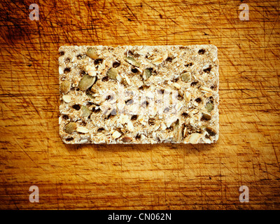 Savoury cracker biscuit with seeds on bread board. - Stock Image
