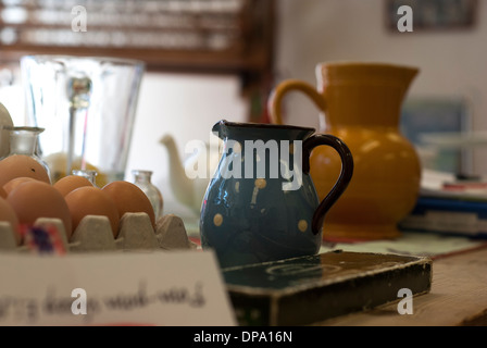 A table top of colourful clutter of jugs, teapots, eggs bit and bobs - Stock Image