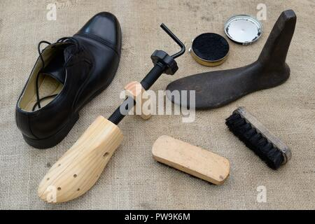 Various items for the maintenance and repair of shoes including, shoe tree, last, polish and brushes alongside a mans black shoe. - Stock Image