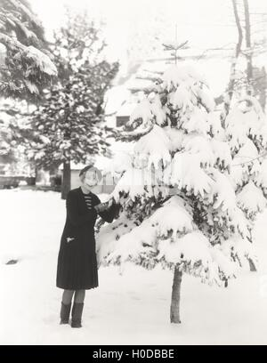 Woman standing by snow covered tree - Stock Image