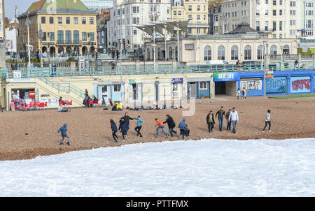 Brighton UK 11th October 2018 - Visitors run from the waves on Brighton beach by the Palace Pier as storms with high winds are forecast to hit some parts of Britain tomorrow Credit: Simon Dack/Alamy Live News - Stock Image