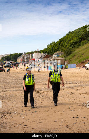 UK, England, Yorkshire, Filey, beach, PCSO and Police officer patrolling on Filey Sands at Coble Landing - Stock Image