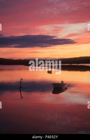 A dramatic sunset reflected on calm water with a  small boat - Stock Image