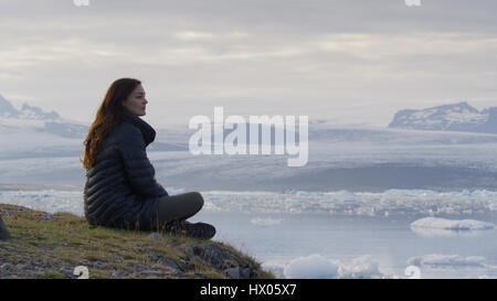Profile view of woman sitting on grassy hilltop overlooking landscape and frozen glaciers in remote still ocean - Stock Image