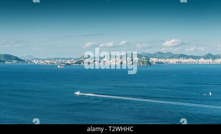 Sailboat on Guanabara Bay, Rio de Janeiro, Brazil with Niteroi city in background. - Stock Image