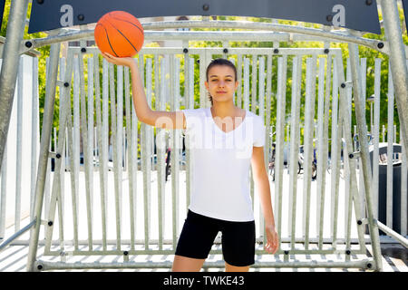 Happy and beautiful teen girl holding a ball to play basketball - Stock Image