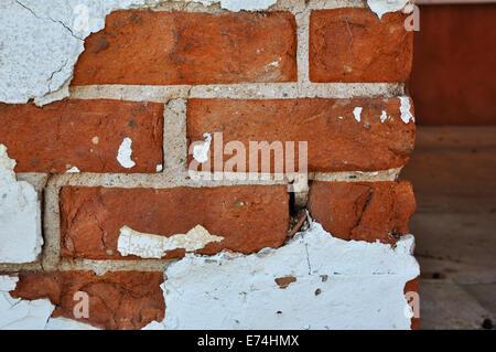 Chipped stucco on brick wall - Stock Image