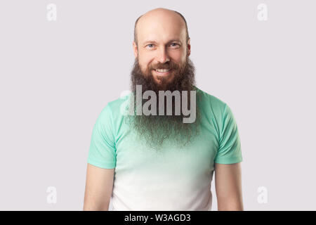 Portrait of happy satisfied middle aged bald man with long beard in light green t-shirt standing and looking at camera with toothy smile. indoor studi - Stock Image