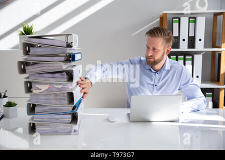 Businessperson Pushing Paper Documents Away And Working With Digital Documents On Computer Instead - Stock Image