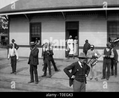 A group of African American people gather on the platform outside a train station in the American south, ca. 1910. - Stock Image