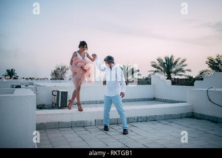 Happy newlyweds walk on roof of house during the honeymoon in Egypt in the evening. - Stock Image