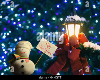 """Snowman figure holding a placard board with stick attached. Text """"Happy New Year!"""". Street lantern wrapped in red - Stock Image"""