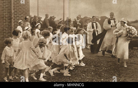 A lovely photograph showing a group of children curtseying to Duchess of York as she arrived to open the new Hospital at Welwyn, Hertfordshire on 24th July, 1934. Although impossible to tell (!) from this picture, the Duchess was wearing an outfit 'in moonlight and turquoise blue'.     Date: 1934 - Stock Image