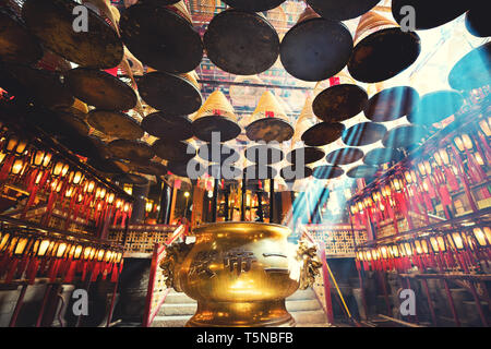 The interior of the Man Mo Temple, Hong Kong, with incense offerings and coils suspended from the ceiling. It is one of the famous temple in Hong Kong - Stock Image