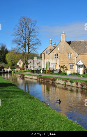 Houses on bank of River Eye, Lower Slaughter, Gloucestershire - Stock Image