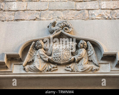 Two angels hold an ancient shield of Barcelona, which contains Masonic symbols, on a dragon. Door of the Convent of San Agustín. Barcelona, Spain. - Stock Image