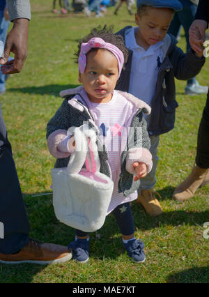 Toddler girl holds her soft white Easter basket as she and her big brother hunt for eggs at the Annual Eggstravaganza, held at Fraser Park and hosted by North and Central Merrick Civic Association (NCMCA). Credit: Ann E Parry/Alamy Live News - Stock Image