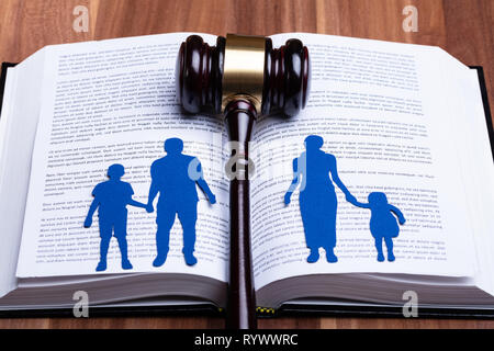 Blue Paper Cutout Of Separated Family On Open Book With Gavel Over Wooden Table - Stock Image