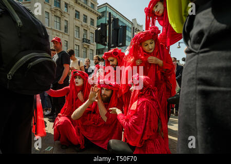London, UK. 19th April 2019. Figures in red to represent the blood of extinct species pose outside the police cordon at Oxford Circus at Extinction Rebellion's Sea of Protest in support to those inside the cordon protecting the pink yacht Berta Cacares. Police were trying to persuade protesters to leave by threatening them with arrest and cutting off those who were locked on around the bottom of the yacht. There were a number of arrests of protesters who refused to leave. A few tried to get the large crowd to protect the yacht, but XR organisers persuaded them not to physically oppose the poli - Stock Image