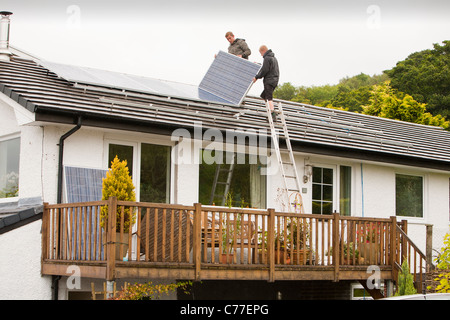 Technicians fitting solar photo voltaic panels to a house roof in Ambleside, Cumbria, UK. - Stock Image