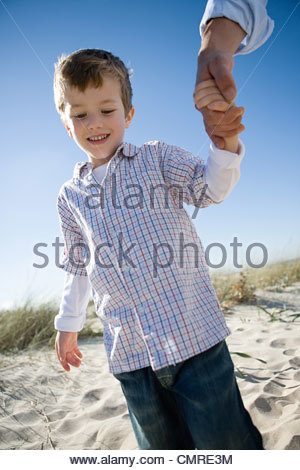 Boy holding hands with parent - Stock Image