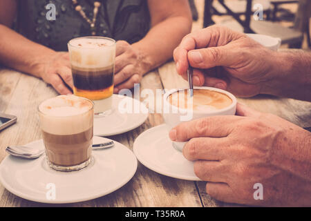 Close-up of hands with coffee cups in a cafe bar enjoying cappuccino for tasty breakfast in the morning - aged hands and mature couple have a break to - Stock Image