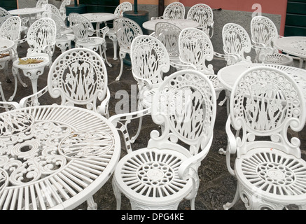 chairs and tables outside a deserted bar in Italy - Stock Image
