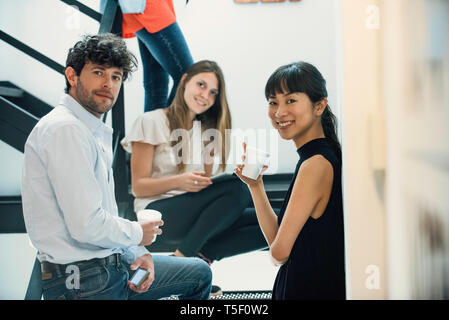 Portrait of smiling business people standing in office - Stock Image