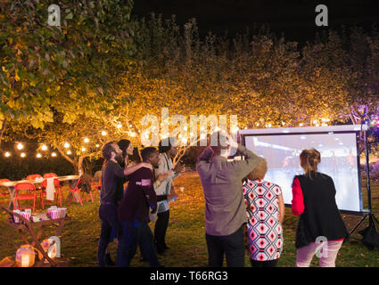 Friends watching basketball game on projection screen in backyard - Stock Image