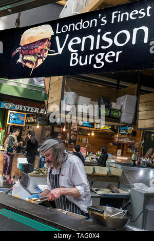 Borough Market renowned ethical novelty Venison Burger Stall with character stallholder preparing a fresh lower fat healthy venison burger snack - Stock Image