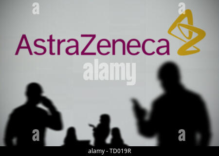 The Astra Zeneca logo is seen on an LED screen in the background while a silhouetted person uses a smartphone in the foreground (Editorial use only) - Stock Image