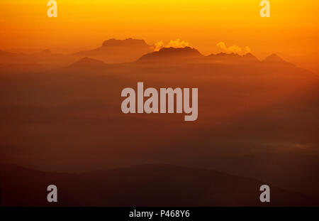 Peaks surrounded by mist at sunset in the French Alps - Stock Image