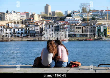 Two young women sitting together eating on the quay looking across the Douro River at Vila Nova de Gaia in Porto, Portugal Europe   KATHY DEWITT - Stock Image