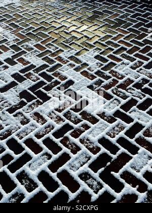 Brick driveway covered with melting snow - Stock Image