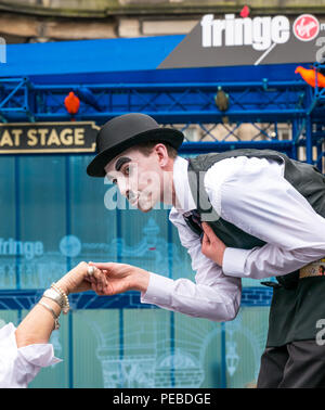 Edinburgh, Scotland, UK. 14th August 2018. Edinburgh Fringe Festival street performer, Royal Mile, Edinburgh, Scotland, United Kingdom. Charlie Chaplin clown impersonator on stilts leaning down to kiss a woman's hand - Stock Image