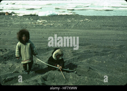 Children playing at the edge of the Arctic Ocean; Point Barrow, Alaska. - Stock Image