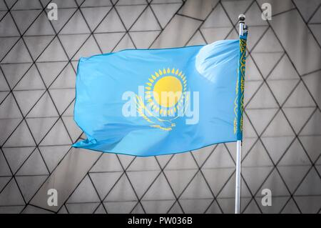 The official flag of the Republic of Kazakhstan waving in the sky against a triangles background. Kazakh flag concept. Kazakhstan Independence Day - Stock Image