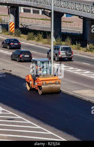 repair of the asphalt road, the machine puts a new coating on the road.Ukraine. Kiev 06.11.2018 - Stock Image